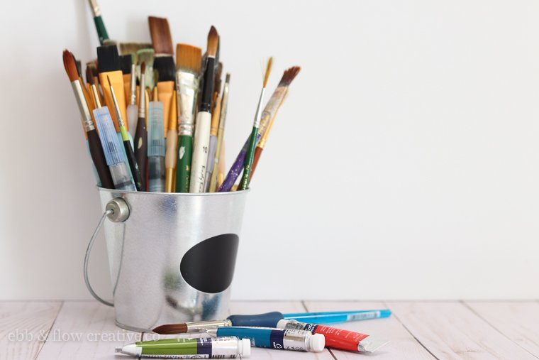 watercolor brushes in tin bucket