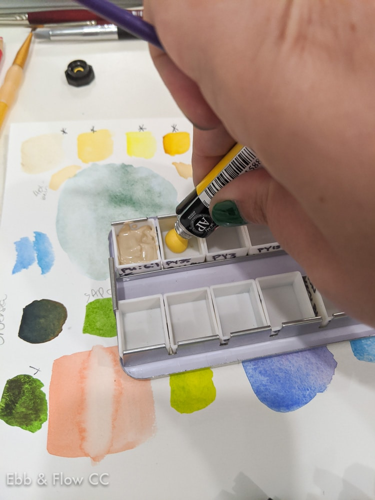 filling a watercolor palette with paint from a tube