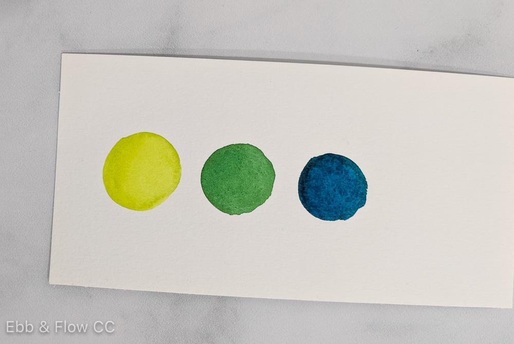 analogous colors scheme of yellow green, green and blue green watercolor swatches on paper
