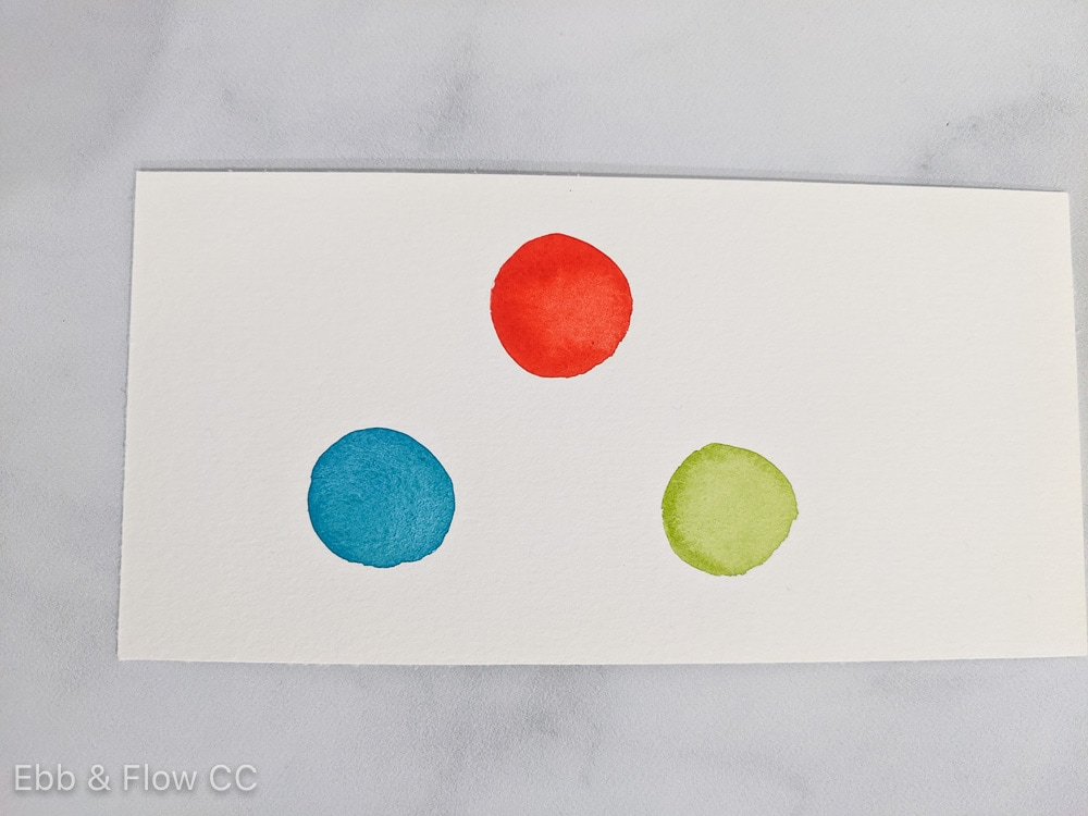 watercolor swatches of red, blue green and yellow green on paper