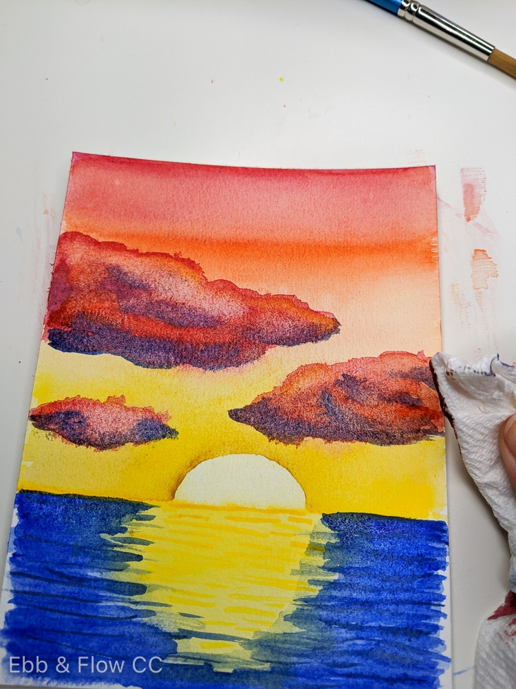 blotting away paint with paper towel