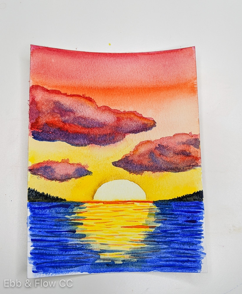 sunset over water painted with watercolors