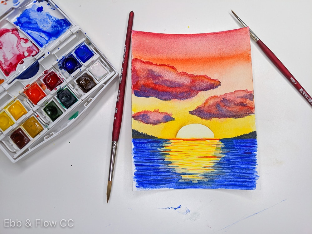 watercolor sunset over water painting with watercolor paint and brushes
