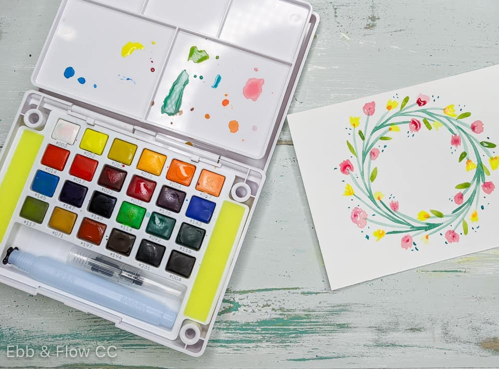 watercolor paint kit and simple floral wreath painting