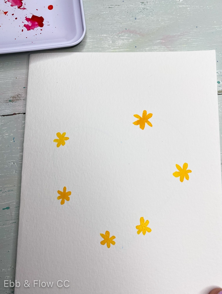 adding yellow flowers to heart shape with paint