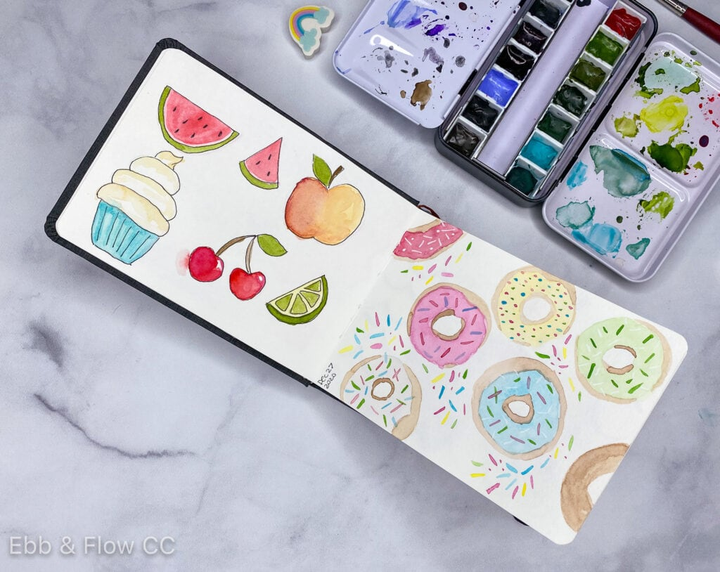 open sketchbook with paintings of fruit and donuts