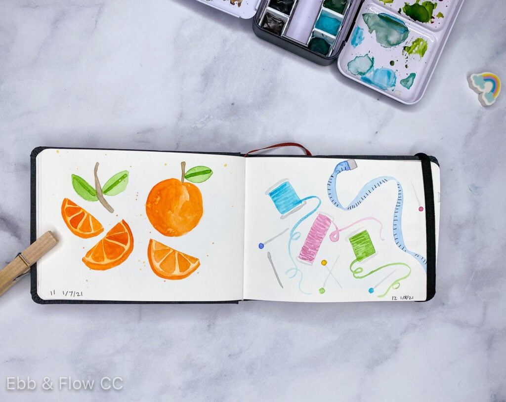open sketchbook with paintings of oranges and sewing supplies