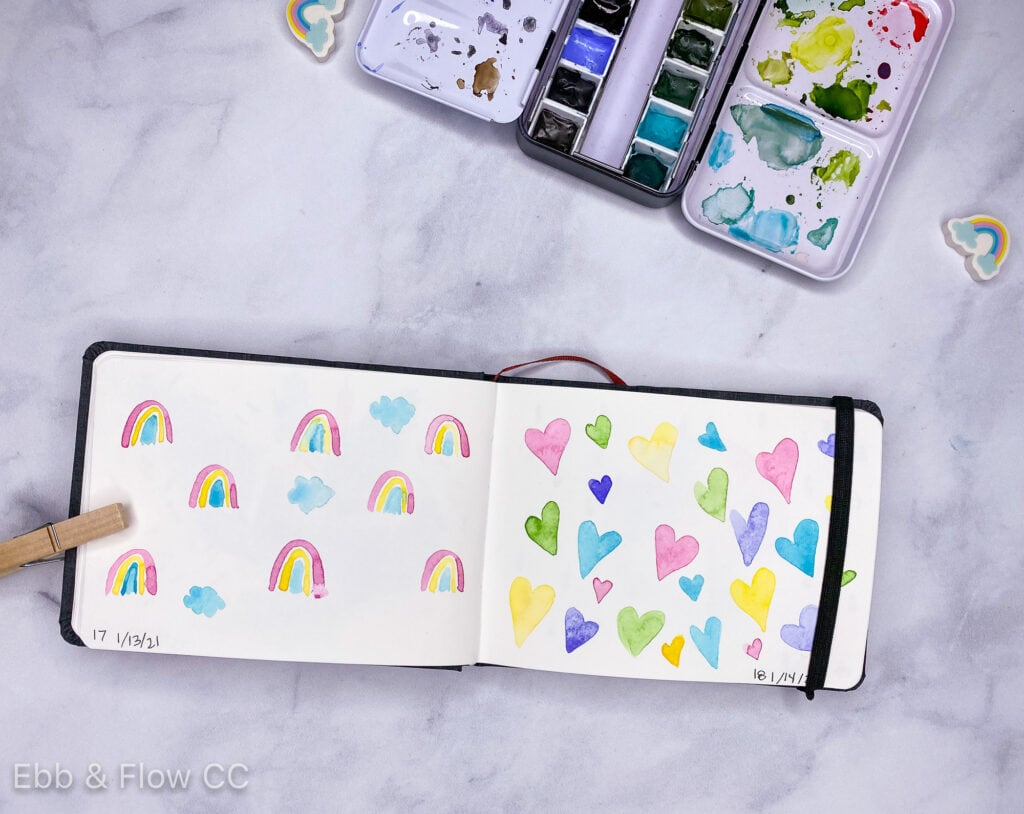 sketchbook with watercolor paintings of hearts and rainbows